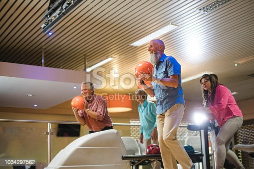 Two senior couples playing ten-pin bowling, the two men are about to bowl.