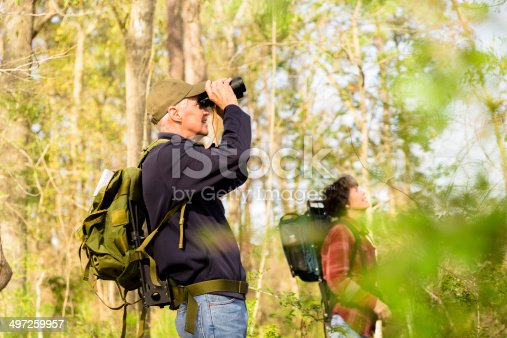 Active senior couple outside hiking in a wooded park area of their community. Man uses binoculars to view wildlife.
