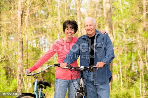 1029243348 istock photo Seniors: Active senior couple outdoors riding bikes. Nature. 497279901