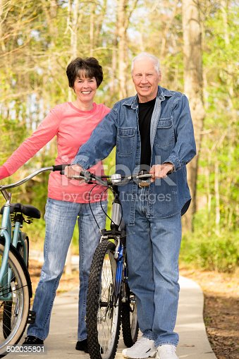 1029243348 istock photo Seniors: Active senior couple outdoors riding bikes. Nature. 502035801