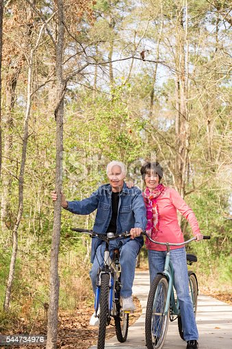 1029243348 istock photo Seniors: Active senior couple outdoors riding bikes. Nature. 544734976
