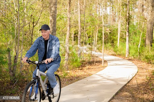 1029243348 istock photo Seniors: Active senior man outdoors riding his bike. Nature. 472180655