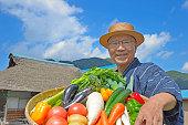 高齢者や古い民家の前に野菜