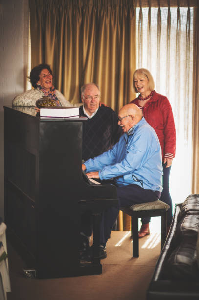 seniors at a piano singing and laughing together - full length of senior people singing together against white stock photos and pictures