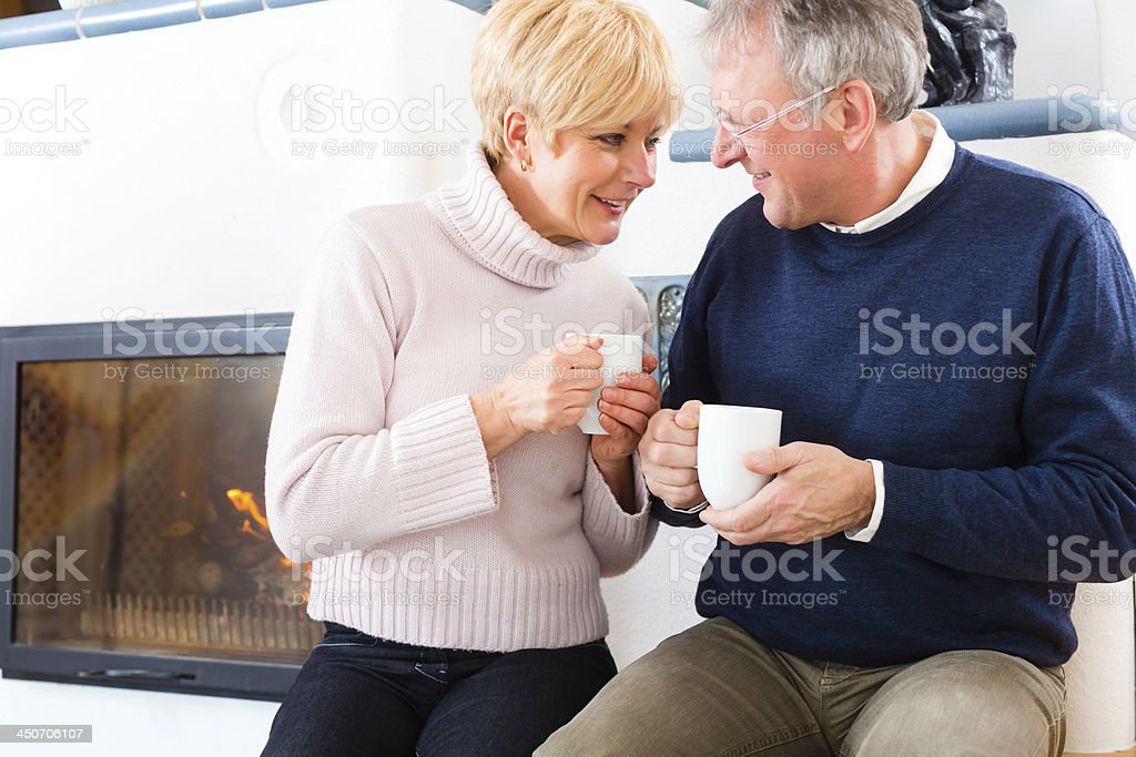 Seniors at home in front of fireplace stock photo
