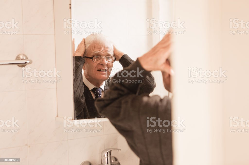 senior man looking in bathroom mirror adjusting his hair stock photo mirror4 mirror