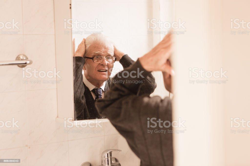 looking in mirror. Beautiful Mirror Senior Man Looking In Bathroom Mirror Adjusting His Hair Stock Photo Throughout Looking In Mirror