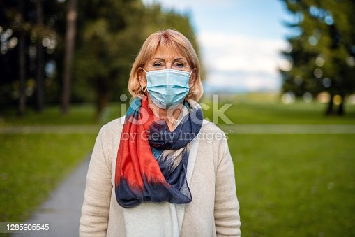 Portrait of a senior woman wearing a medical mask outdoors