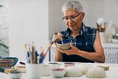 Senior woman decorating bowl made of clay on ceramics workshop.