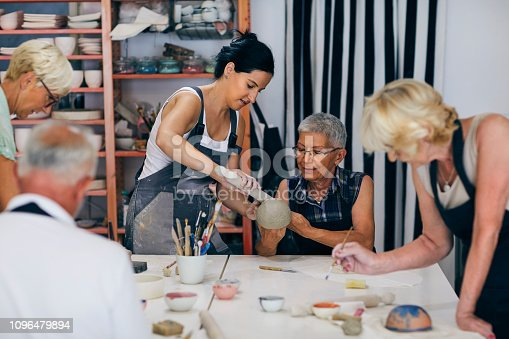 Group of seniors  on ceramic workshop working with instructor.