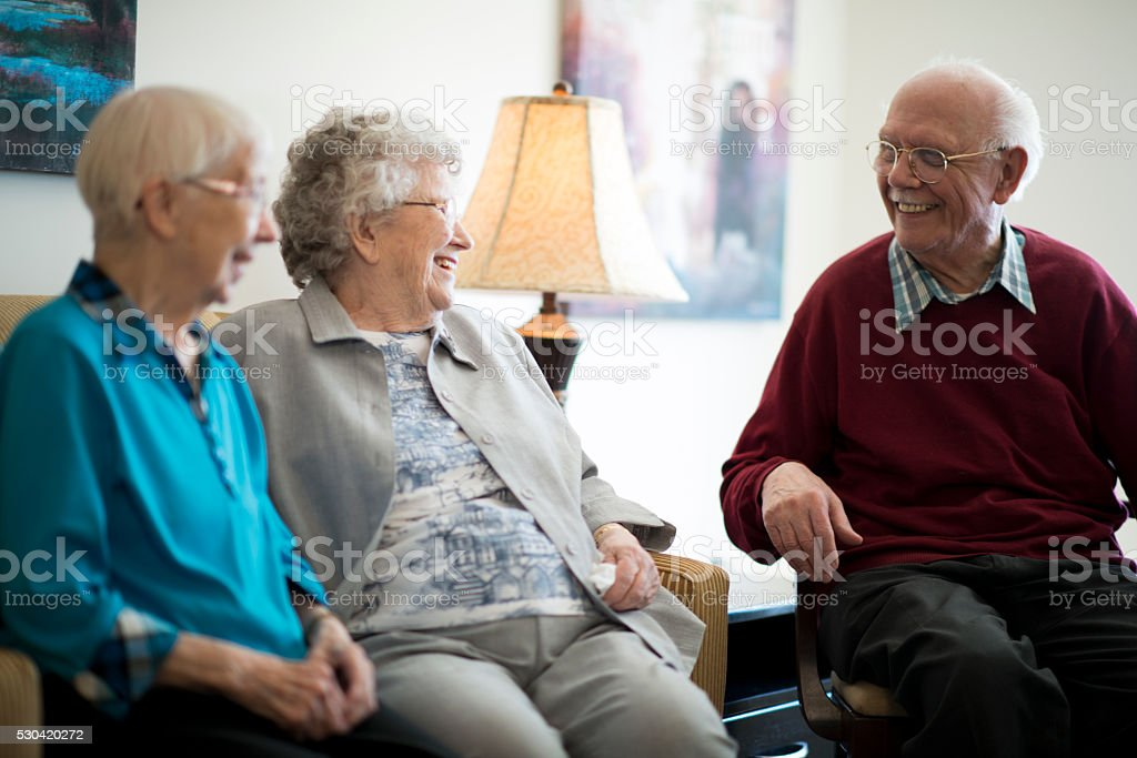 A group of senior adults are sitting in a nursing home and are...