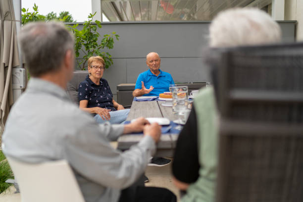 seniors chatting outdoors in garden during afternoon tea stock photo