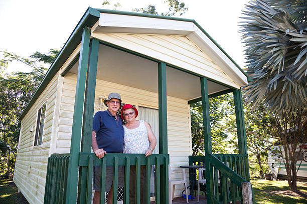 Seniors Couple in front of holiday cabin Happy retired senior couple standing in front of a holiday cabin aa affectionately with arms around each other. trailer park stock pictures, royalty-free photos & images