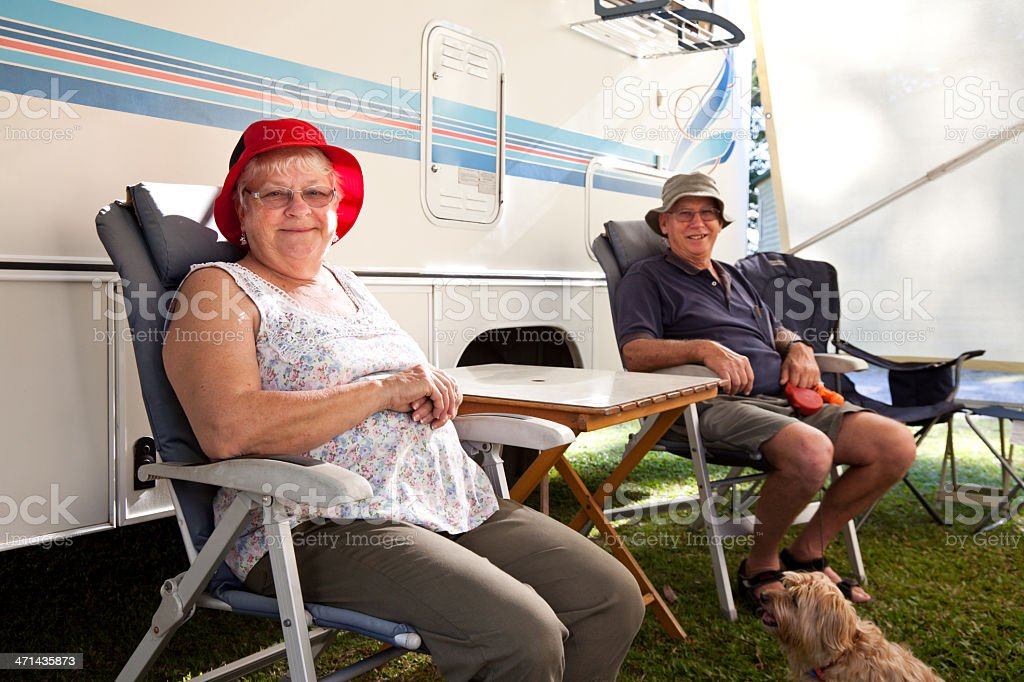 Seniors Couple sitting outdoors with Motorhome RV stock photo