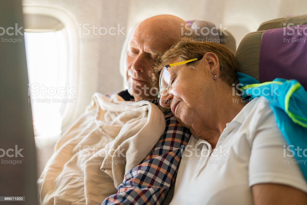 Seniors - couple sleeping in airplane stock photo