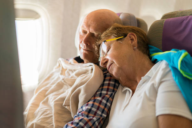Seniors - couple sleeping in airplane inflight - senior couple tourists in their seventies sleeping in airplane seat together jet lag stock pictures, royalty-free photos & images