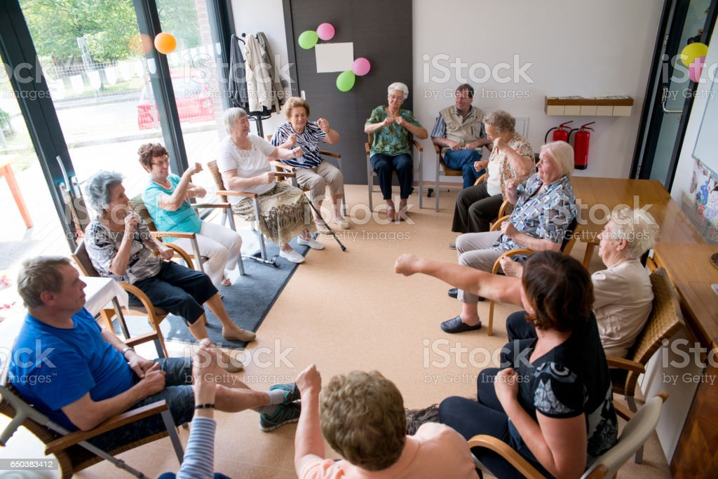Seniors Doing Relaxation Exercises In The Elderly Day Care Center stock photo