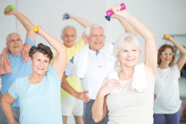 пожилые люди делают силовые упражнения - class стоковые фото и изображения