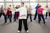 Group of senior adults practicing tai chi with an instructor in the community center., blurred motion.