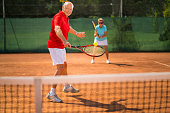 active senior couple tennis players playing double on a clay court. Logo for racket and clothing created by ourselves therefore property released