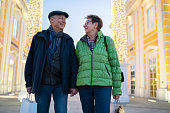 happy senior couple 70 to 75 years old standing together outdoors on winter christmas shopping evening in luxury designer outlet center shopping mall smiling at each other, shallow focus, background blurred