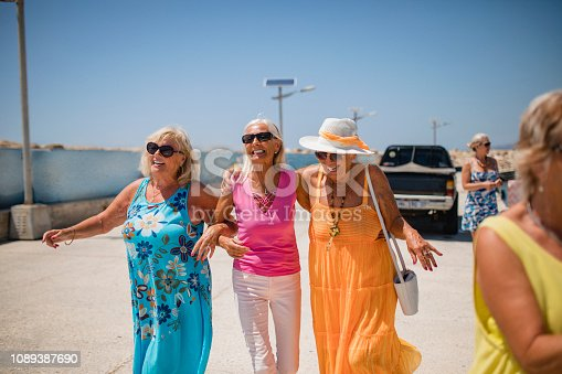 A wide-view shot of a group of senior female friends walking arm in arm on a hot summer's day in Cyprus.