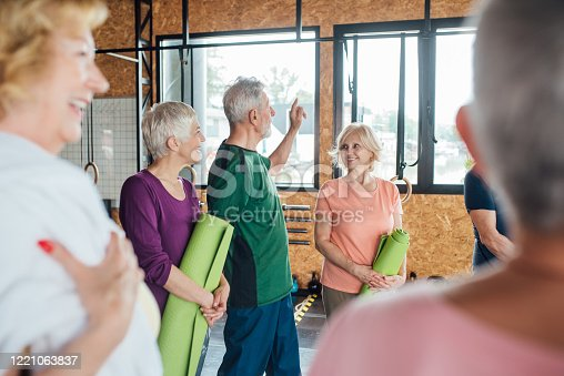 1047537292 istock photo Seniors gathering to practice yoga together 1221063837