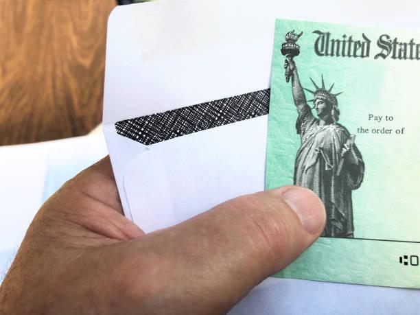 Senior's hand holding a Federal treasury check stock photo