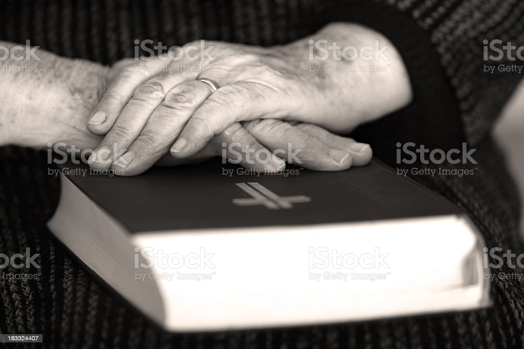 Senior's hands on old book royalty-free stock photo