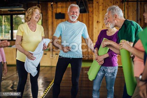 1047537292 istock photo Seniors having fun before their weekend yoga class 1221063857