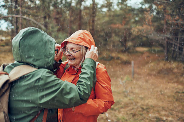 Seniors Hiking in the Rain Close up of two female seniors hiking through the forest waterproof clothing stock pictures, royalty-free photos & images