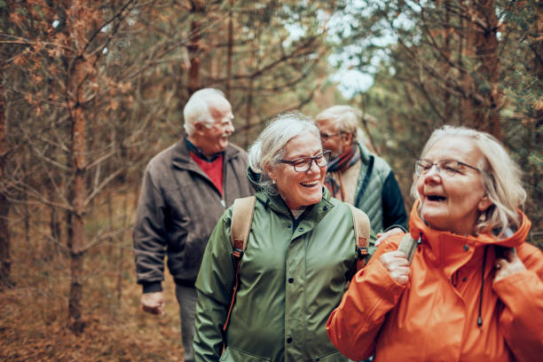 seniors hiking through the foerst - old people stock pictures, royalty-free photos & images