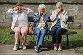 Three senior women are sitting on a bench in a public park, each of them imitating the three wise monkeys; 'see no evil, hear no evil, speak no evil.'