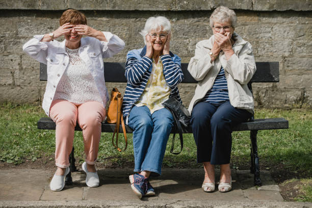 Seniors Imitating the Three Wise Monkeys Three senior women are sitting on a bench in a public park, each of them imitating the three wise monkeys; 'see no evil, hear no evil, speak no evil.' hear no evil stock pictures, royalty-free photos & images