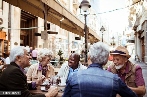 Close up of a group of seniors relaxing in a cafe after exploring the city