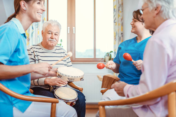 Seniors in nursing home making music with rhythm instruments stock photo