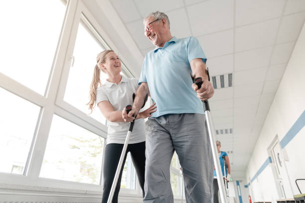 Seniors in rehabilitation learning how to walk with crutches stock photo