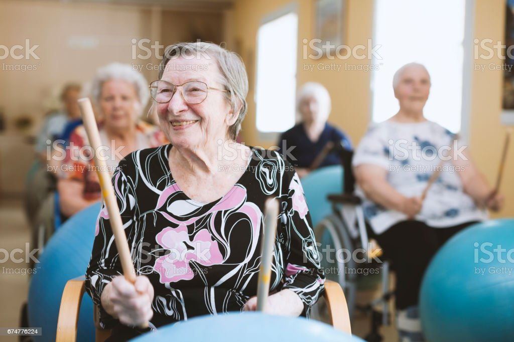 Seniors In The Nursing Home Having Relaxation Exercises With Fitness Ball stock photo