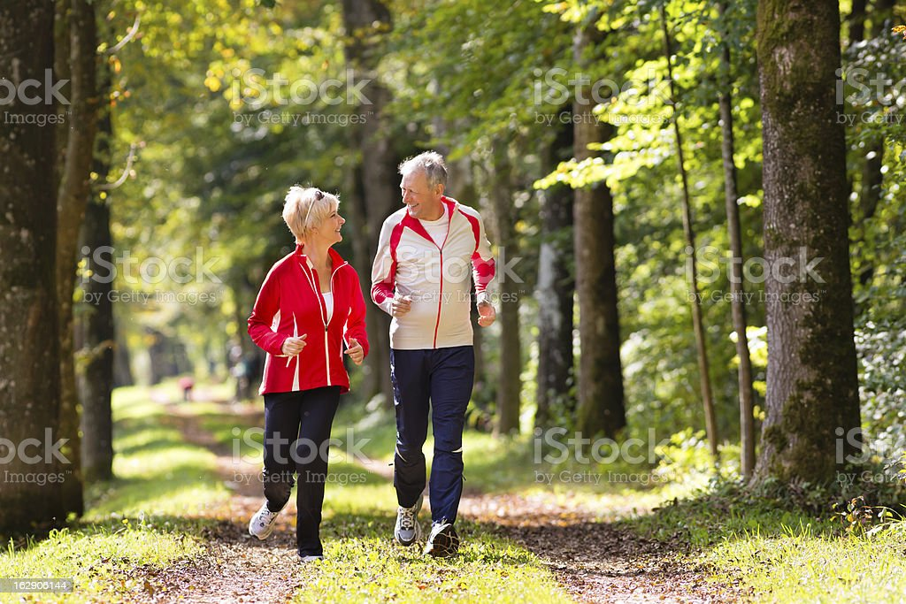 Seniors jogging on a forest road stock photo