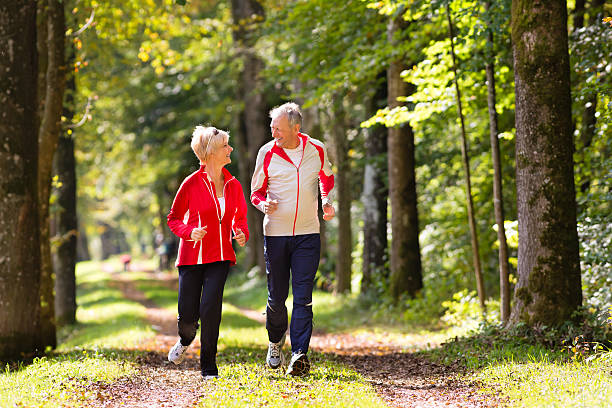 seniors jogging on a forest road - active seniors stock photos and pictures