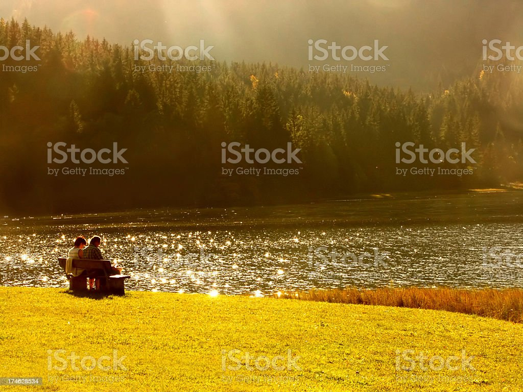 seniors make pause on lake at sunset royalty-free stock photo