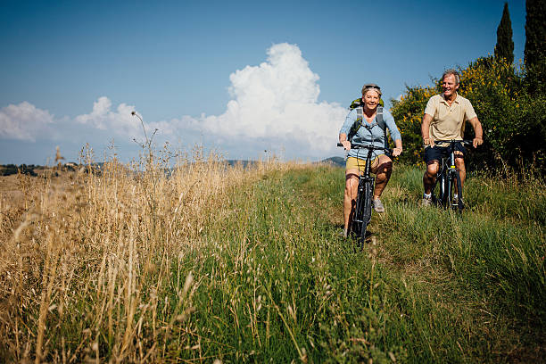 seniors on mountain bikes in the countryside - italienische lebensart stock-fotos und bilder