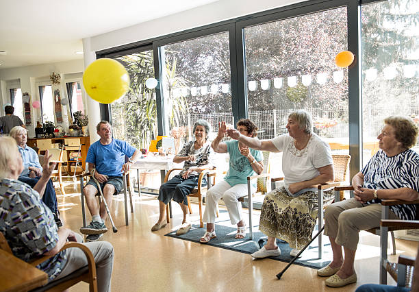 seniors participating in group activities in adult daycare center - seniorenbetreuung stock-fotos und bilder