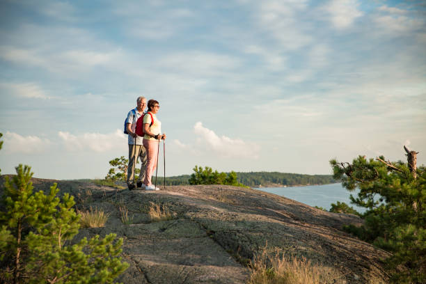 Seniors Active senior couple hiking on the top of rock, exploring. Mature man and woman Happily smiling. Nordic walking, trekking. Scenic view of gulf and sea. Healthy lifestyle. Finland. nordic walking stock pictures, royalty-free photos & images