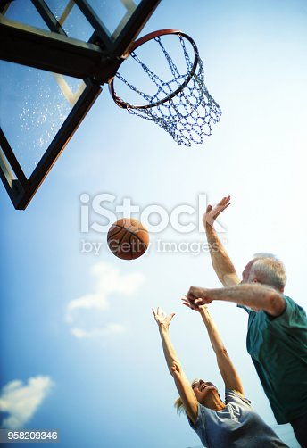 Closeup low angle view of couple of seniors playing basketball in a park on a sunny summer afternoon. Vertical