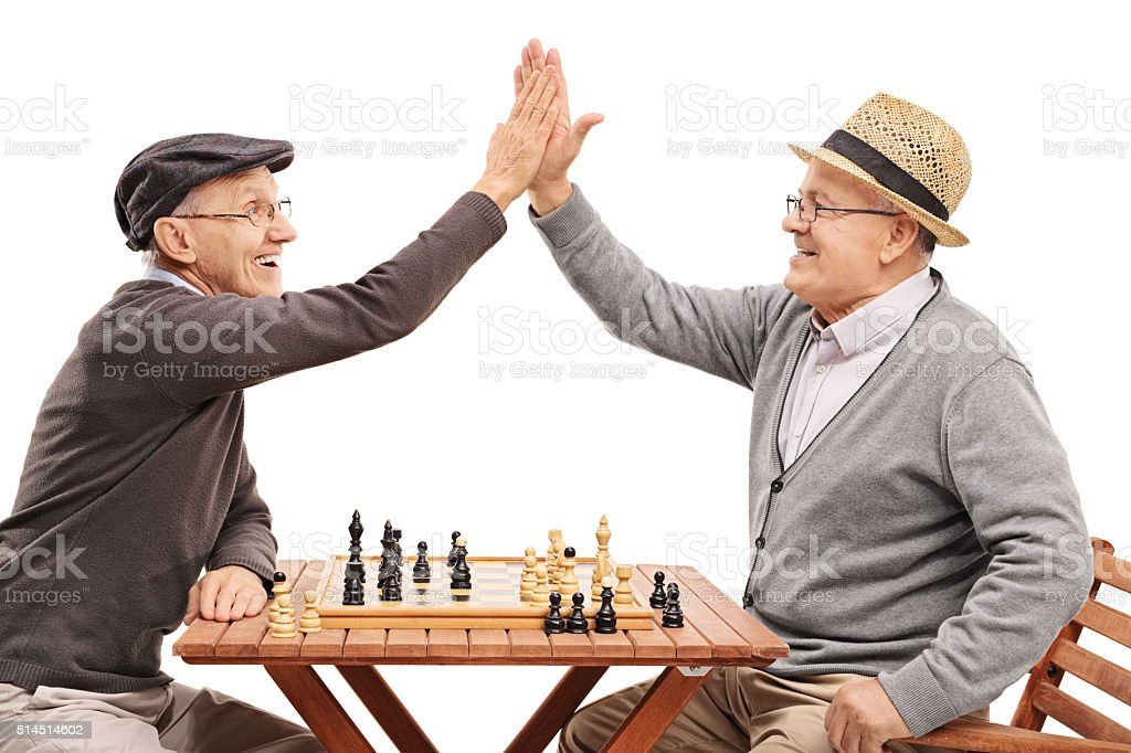 Seniors playing chess and high-five each other stock photo