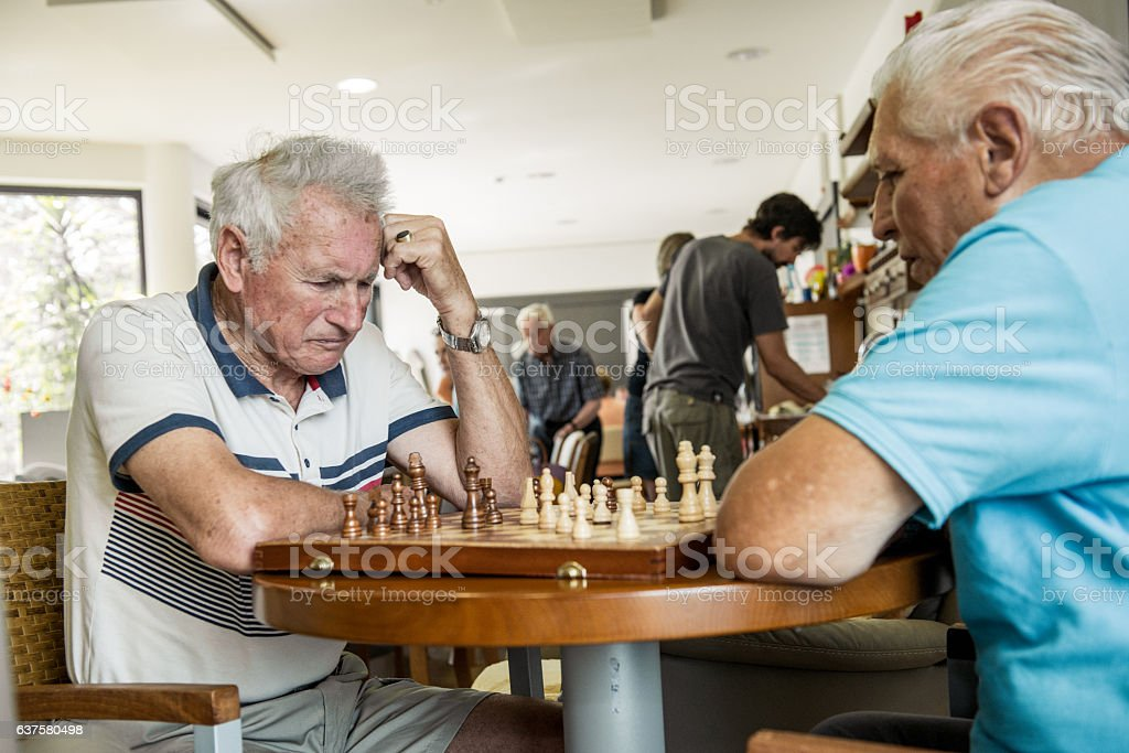 Seniors Playing Chess in an Elderly Daycare Center stock photo