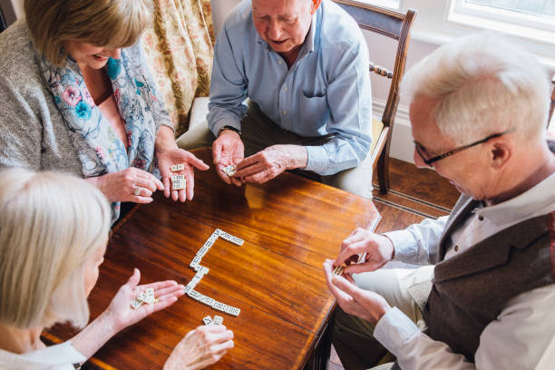 seniors playing dominoes - game of life stock photos and pictures