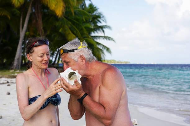 senioren spielen mit counch telefon auf insel isla pelicano in karibik sehen - senior bilder wasser stock-fotos und bilder