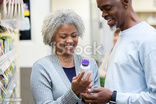 Senior adult African American man and woman are reading labels on bottle of medication or vitamins while shopping together in supermarket or pharmacy.